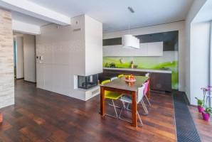 Salon z kominkiem z półotwartą kuchnią w stylu nowoczesnym.