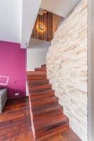 Drewniane schody w salonie prowadzące na piętro, zabezpieczone taflą szklaną, pod schodami schowek.