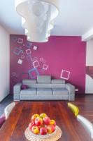Wypoczynek w salonie ze ścianą w barwne wzory; dwa kwadraty są jednocześnie lampkami.