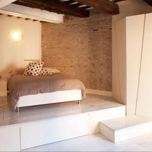 Sypialnia na podeście, który spełnia też funkcję dodatkowej strefy przechowywania. Fot. Archifacturing.