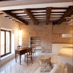 Największą ozdobą niewielkiego wnętrza jest belkowanie sufitu oraz piękna stara cegła na ścianie. Fot. Archifacturing.