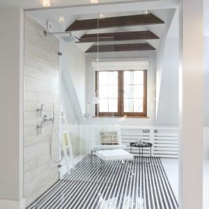 Kabina prysznicowa z imponującym przeszkleniem wykonana została na zamówienie. Posadzkę wyłożono czarno – białą mozaiką w pasiasty wzór. Wyposażenie: mozaika Tubądzin. Fot. Bartosz Jarosz