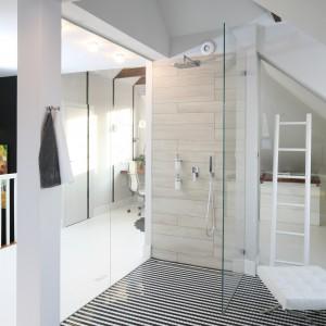 Kabina wyposażona została w podtynkową baterię prysznicową. Płytki, na ścianie z instalacją, ułożono naprzemiennie nawiązując do sposobu montowania cegieł, których motyw powtarza się w sąsiednich pomieszczeniach. Fot. Bartosz Jarosz