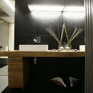Łazienka z wanną w czerni i złamanej bieli. Chłód kolorystyczny doskonale równoważą materiały imitujące drewno. Fot. Marcin Onufryjuk.