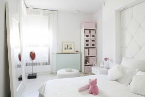 Wielkie lustro w białych ramach oparto o ścianę naprzeciwko łóżka. Fot. Bartosz Jarosz.