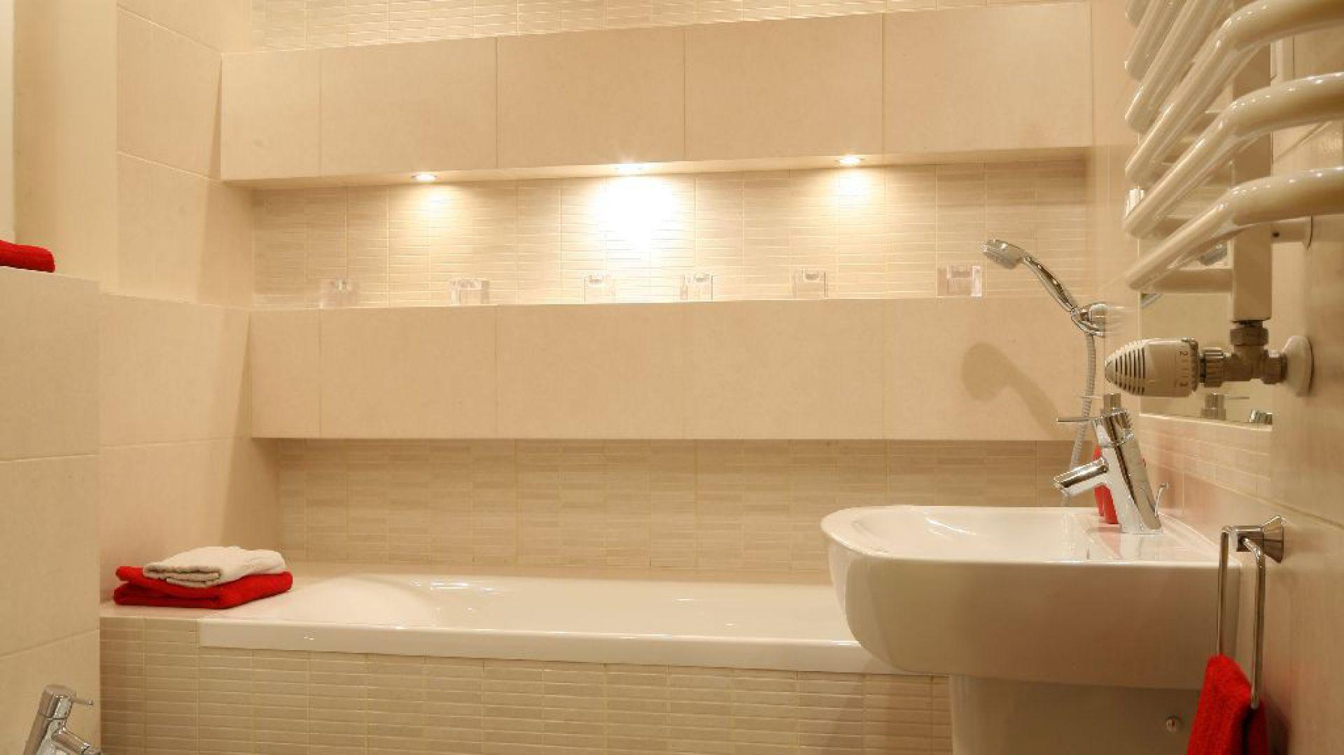 Łazienka jest jasna i spokojna. Czerwone dodatki stylistycznie spajają ją z pozostałymi elementami mieszkania. Wyposażenie: umywalka Cersanit / bateria Hansgrohe / wc, bidet Cersanit. Fot. Bartosz Jarosz.