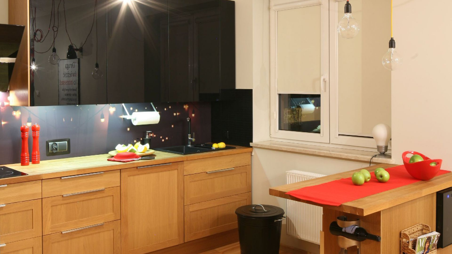 Kuchnię od części wypoczynkowej oddziela niewysoki barek, który jednak nie zamyka otwartej przestrzeni. Wyposażenie: oświetlenie wiszące CablePower / podłoga deska barlinecka jesion. Fot. Bartosz Jarosz.