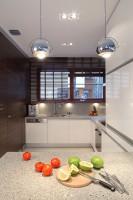 Zabudowana lewa ściana kuchni w ciemnej płycie meblowej skrywa drzwi do pomieszczenia gospodarczego. To również wygodna, podręczna spiżarka. Fot. Bartosz Jarosz.