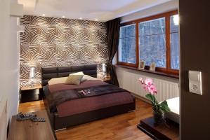 Tapeta w sypialni przywołuje na myśl dzikie afrykańskie klimaty. Całość, przybrana w ciepłe kolory ziemi i natury, działa odprężająco. Fot. Bartosz Jarosz.