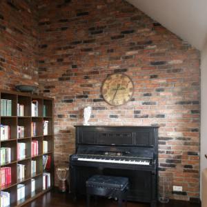 Zegar przywieziony z Francji, mimo iż na wskroś współczesny, dostojnie prezentuje się na tle ściany wykończonej prawie stuletnią cegłą. Pianino odziedziczone po babci pięknie uzupełnia tę część salonu. Fot. Bartosz Jarosz.