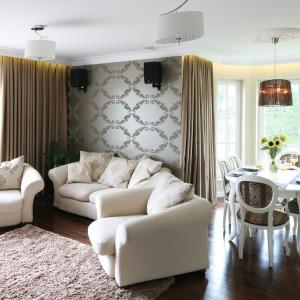 Miejsce na rodzinną jadalnię wydzielono w przestrzeni salonu. Znajduje się ona w przeszklonym wykuszu, dzięki czemu praktycznie zawsze jest pełna światła. Ładny, stylizowany stół w białym kolorze doskonale prezentuje się z tapicerowanym krzesłami w odcieniach brązu. Całość spina dekoracyjne oświetlenie. Projekt: Katarzyna Merta-Korzniakow. Fot. Bartosz Jarosz.