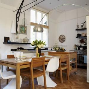 Prosty, nieco rustykalny styl połączony został w tej jadalni z nowoczesnymi akcentami, natomiast dominująca biel z naturalnymi materiałami. Ponadczasowe krzesła Vernera Pantona doskonale pasują do drewnianego stołu oraz ogromnej lampy nie wiszącej, lecz podłogowej. Fot. Brent Darby/Narratives.