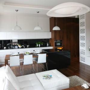 Strefa dzienna jest całkowicie otwarta. Granicę, jednakże tylko symboliczną, między kuchnią a salonem wyznacza podwieszony sufit, elegancka wyspa oraz fornirowany, orzechowy stół, pełniący rolę jadalni. W tym wnętrzu drewniane elementy połączono z elementami lakierowanymi na wysoki połysk w kolorze białym i czarnym. Oba materiały doskonale się uzupełniają i idealnie do siebie pasują. Projekt: Agnieszka Ludwinowska. Fot. Bartosz Jarosz.