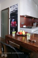 Kuchnia w stylu minimalistycznym, białe fronty szafek zlewają się optycznie z jasnymi ścianami. Stół z grubego, litego drewna palisandrowego. Dekoracja ścienna wykonana z podświetlanego pleksi z naniesionym wydrukiem.