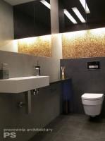 Toaleta w stylu nowoczesnym, w ciemnej tonacji. Akcentem ocieplającym wnętrze jest drewniana mozaika podświetlona światłem ledowym umieszczonym pod szafką z czarnymi frontami. Duże lustro zlicowane z płytkami powiększa optycznie małą przestrzeń.