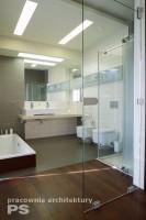 Pokój kąpielowy w stylu nowoczesnym. Wejście wykonane ze szkła przeźroczystego pokazuje przenikanie się gresowych płytek z drewnianą podłogą wychodzącą z sypialni. Wanna wpuszczona w posadzkę, obudowana drewnem egzotycznym. Umywalka podwójna, zamontowana na blacie z marmuru. Duże lustro nadaje lekkości i przestrzeni. Nad nim wykonano świetliki sufitowe.