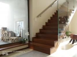 Klatka schodowa wykończona w litym drewnie egzotycznym. Stopnice i podstopnice tworzą zwarty układ dywanowy schodów. Przeszklona balustrada rozpięta jest miedzy biegiem schodów a sufitem. Detale wykonano ze stali nierdzewnej.