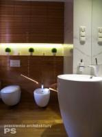 Łazienka wykończona drewnem z niszą dekoracyjną na roślinność. W projekcie zastosowano obłe kształty misek i umywalki, płynnie harmonizujące ze słojami drewna. Posadzka w łazience z litego drewna teakowego.