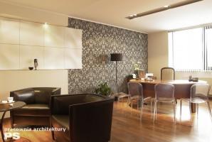 Wnętrze kancelarii łączące ze sobą styl retro z nowoczesnym. Panele gipsowe na ścianie komponują się z tapetą w neobarokowe wzory. Podłoga wykończona drewnem egzotycznym. Krzesła z przeźroczystego akrylu nadają wnętrzu lekkości.