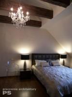 Sypialnia w stylu retro. Na suficie podświetlane jętki dachowe, wykończone stylizowanym na stare drewnem dębowym. Żyrandol kryształowy przeźroczysty wraz z fotelem podkreślają styl wnętrza. Podłoga z drewna egzotycznego dodaje ciepła pomieszczeniu.