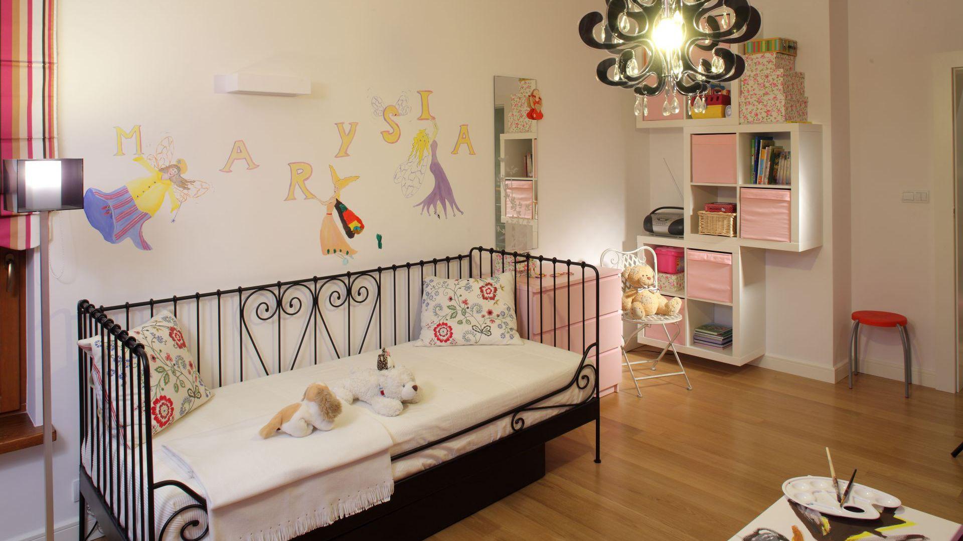 Ubrania dziewczynka skrywane są w różowej komodzie, natomiast książki i drobiazgi - na półkach naściennych. Fot. Bartosz Jarosz.