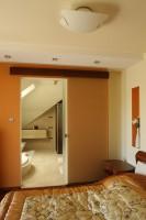 Ciepła kolorystyka sypialni znajduje swoją kontynuację w kremach i brązach, które pojawiają się w łazience. Po otwarciu przesuwnych drzwi pomieszczenia tworzą jedną całość. Fot. Bartosz Jarosz.