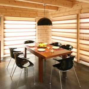 Prosty drewniany stół fajnie pasuje do czarnych, plastikowych krzeseł i lamy, również w czarnym kolorze. Z jadalni można wyjść bezpośredni na taras. Fot. Bartosz Jarosz.