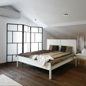 """Obszerna sypialnia jest utrzymana w odcieniach bieli i beżu. Przestronne  pomieszczenie  z dużą dawką """"miękkiego"""" światła koi zmysły i ciało.  Fot. Bartosz Jarosz."""