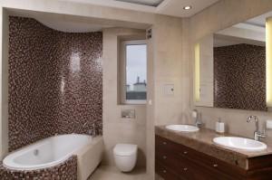 Szafkę z umywalkami dla dwojga wykonano na zamówienie z granitu i drewna merbau. Kolorystyka kamienia jest dopasowania do odcieni szaro-brązowej mozaiki z perłowym połyskiem. Fot. Bartosz Jarosz.