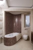 Falujące powierzchnie mozaiki otulają owalną wannę. Mieniące się kostki przyciągają wzrok, dzięki czemu sedes schodzi na drugi plan. Fot. Bartosz Jarosz.