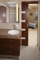 Łazienkę i sypialnię dzielą przesuwne, chowane w ścianie drzwi. Po ich otwarciu, oba pomieszczenia tworzą jedną, stylistycznie spójną przestrzeń. Fot. Bartosz Jarosz