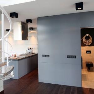 Metalowe, kręcone schody doskonale wpisują się w industrialny klimat całego wnętrza. Fot. Bartosz Jarosz.