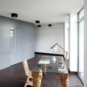 """""""Kącik"""" do pracy w strefie wejściowej. Biurko łączy funkcje użytkowe z dekoracyjnymi. Każdą nogę stołu inaczej wyrzeźbił Paweł Gruner. W tle widoczny jest szary kubik. Fot. Bartosz Jarosz."""