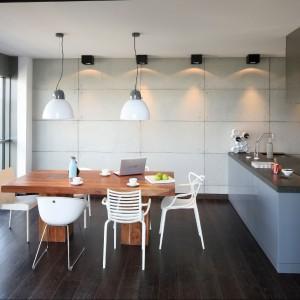 Do dużego, masywnego, drewnianego stołu zostały dobrane delikatne krzesła w kolorze białym. Co ważne, każde z nich jest inne, co przełamuje prostą formę wnętrza. Fot. Bartosz Jarosz.