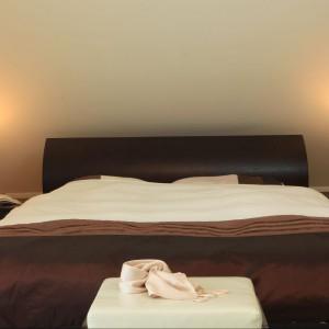 Ciepłe kolory sypialni skontrastowane z bielą dywanu i toaletką pani domu ubrały wnętrze w szyk i nutę glamour. Fot. Green Canoe.
