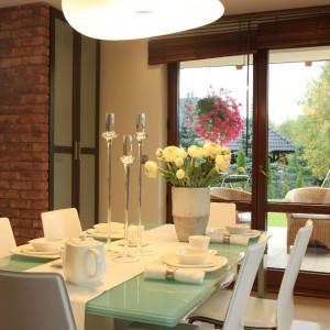 Szklany stół marki Calligaris kontrastuje z ciemną zabudową kuchenną oraz ceglanymi ścianami. Fot. Green Canoe.
