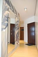 Ścianę zdobi tapeta z motywem liści. Jasna podłoga o ciepłym, słomkowym odcieniu to deski bambusowe.