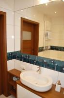 W niewielkiej łazience wykorzystane zostało miejsce na szafki i półki, znajduje się w niej wygodna szafka pod umywalkę,