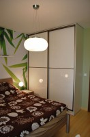 Szafa z przesuwanymi drzwiami została zaprojektowana do sypialni na wymiar.