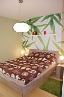 W sypialni o zielonej kolorystyce, powtórzony został motyw liści na fototapecie.
