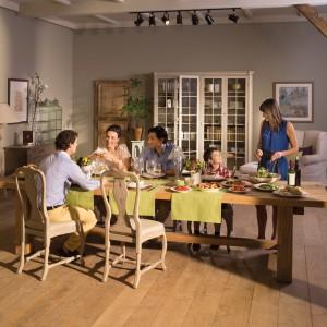 Duży, prosty w formie drewniany stół zestawiony został z eleganckimi, lekkimi krzesłami w kremowym kolorze. Oba produkty pochodzą z kolekcji marki Flamant.