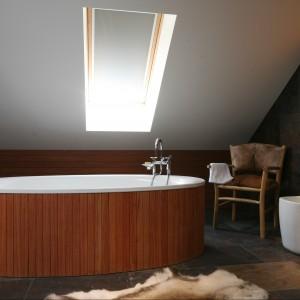 W łazience zastosowano płytki z naturalnego kamienia. W połączeniu z bielą armatury łazienkowej i ciepłą, teakową obudową wanny uzyskano efekt przyciągający wzrok. Fot. Bartosz Jarosz.