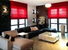 Dom w prostym nowoczesnym stylu. Dodatki koloru czerwonego ożywiają wnętrza.