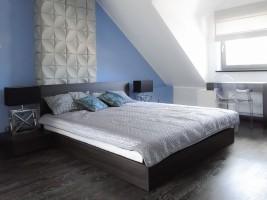 Dom w prostym nowoczesnym stylu. Dodatki kolorów niebieskiego i czerwonego ożywiają wnętrza. Ciekawe rozwiązanie w sypialni- za niebieską ścianką ukryta jest kabina prysznicowa, a przejścia po jej obu stronach można zamknąć przesuwnymi białymi panelami.