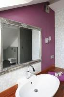 Fioletowa ściana, na której powieszono antyczne lustro ma za zadanie przełamać dominację grafitu i wprowadzić element przytulności, w czym pomaga jej teakowy blat podumywalkowy. Fot. Bartosz Jarosz.