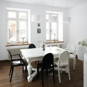 Wyposażenie jadalni stanowi odważnie skompletowany zestaw mebli: odrestaurowany, pomalowany na biało drewniany stół z rzeźbionymi nogami oraz nowoczesne designerskie krzesła projektu Philippe Starca. Projekt: Konrad Grodziński. Fot. Bartosz Jarosz.