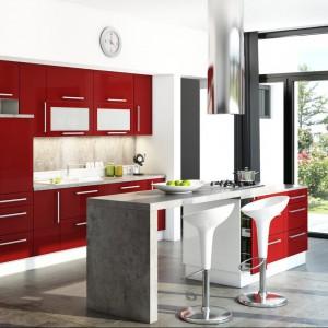 Kuchnia Martyna z frontami lakierowanych na wysoki połysk w intensywnym czerwonym kolorze, grubym sześciocentymetrowym blatem w kolorze betonu oraz z wygodnymi, podłużnymi aluminiowymi uchwytami. Uzupełnieniem czerwonych frontów są białe tafle korpusów i matowe szyby witryn. Wycena indywidualna, Layman.