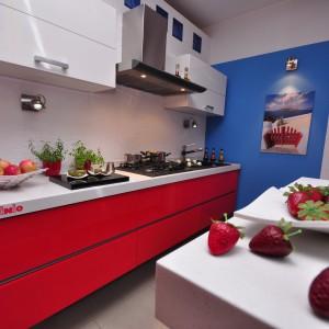 Nowoczesna kuchnia w połysku, w której przeciwwagą dla białych frontów szafek wiszących jest ognista czerwień w dolnych szufladach. Razem tworzą one dynamiczny kontrast, który uzupełnia dodatkowo błękit na ścianie. Wycena indywidualna, Pinio.
