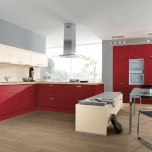Meble kuchenne z kolekcji Alva w dwóch kolorach matowych frontów: czerwonym oraz magnolii. Blat jest z laminatu w ciepłym, jasnym odcieniu klonu. Wycena indywidualna, Wellmann.