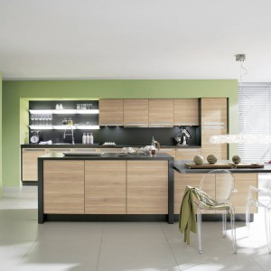 Nowoczesne meble kuchenne z programu Alnoplan. Górne i dolne szafki oraz wysoka zabudowa zapewniają sporą ilość miejsce na przechowywanie. Fronty w spokojnym, stonowanym kolorze jasnego klonu i szary, równie subtelny blat, ładnie ożywia zielona ściana. Wycena indywidualne, Alno.